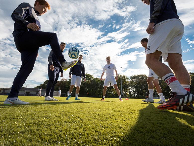 Penn State Abington Men's Soccer Team juggling soccer ball