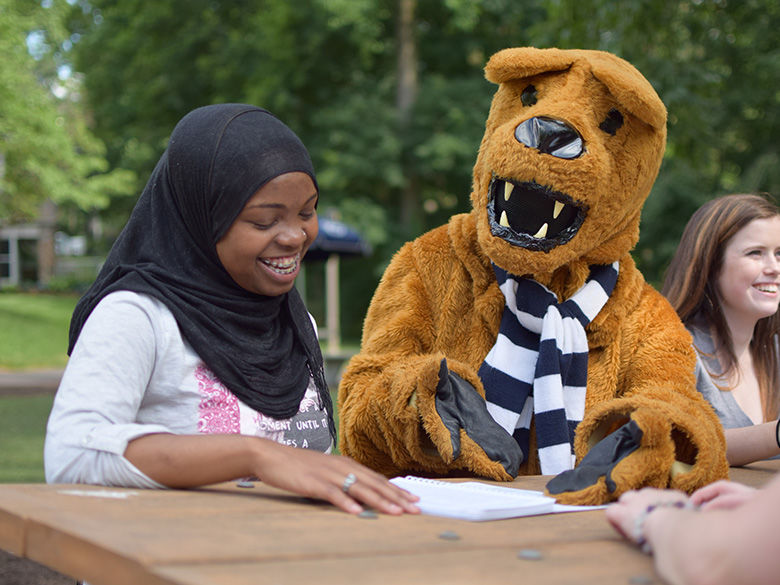 student with Nittany Lion on bench outside