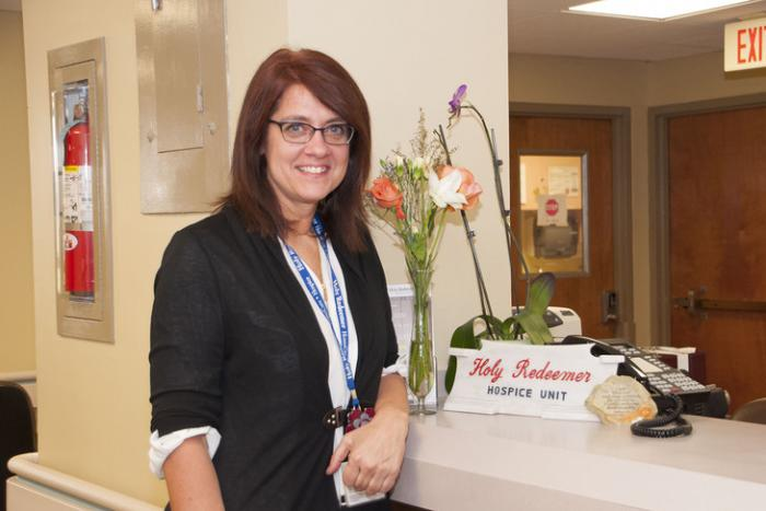 Nurse Donna standing by the intake desk at a hospital