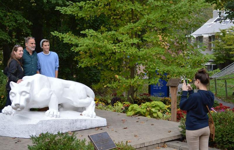 family taking photos at the lion shrine