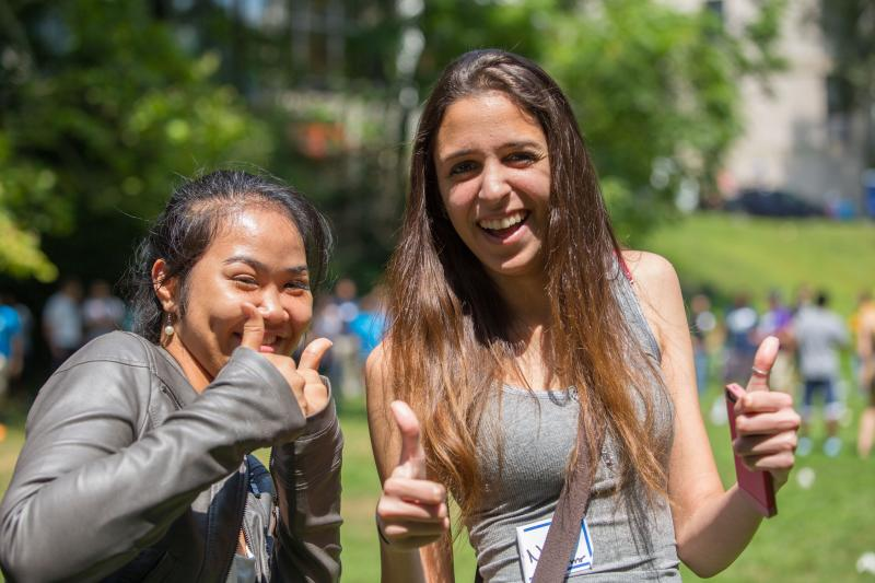 two female students giving thumbs up