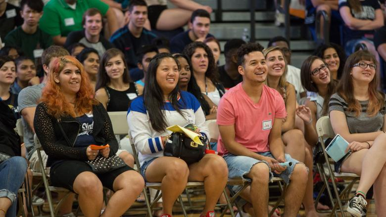 students sitting in stands in gymnasium
