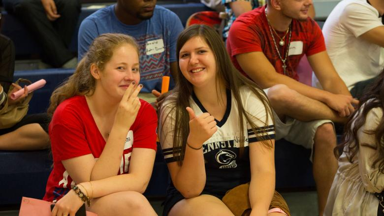 two girls in the stands with a thumbs up and peace sign